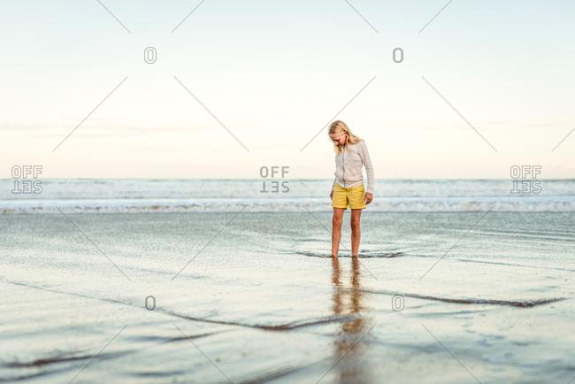 Tween girl standing in water at a beach
