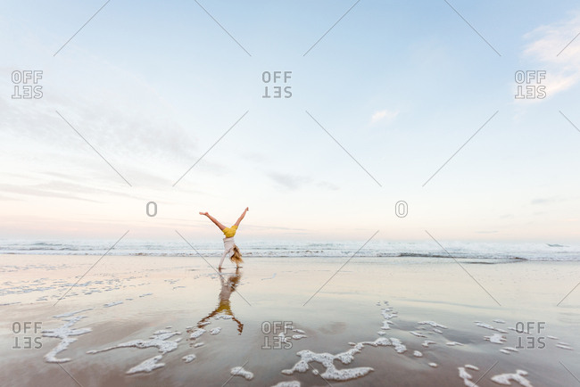 Preteen girl doing a cartwheel at beach with reflection