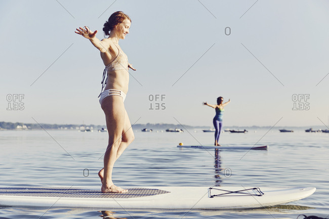 Two women doing yoga on SUP boards early in the morning