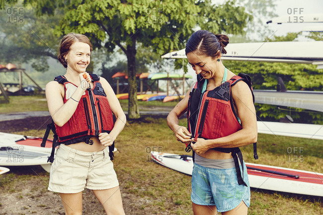 Two young women getting ready to go standup paddle boarding