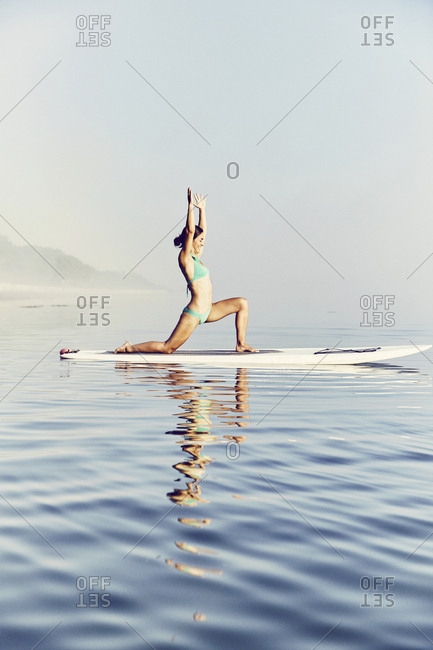 Young female standup paddle boarder doing yoga at sunrise in the fog