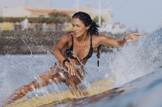 Full length action of female surfer in bikini