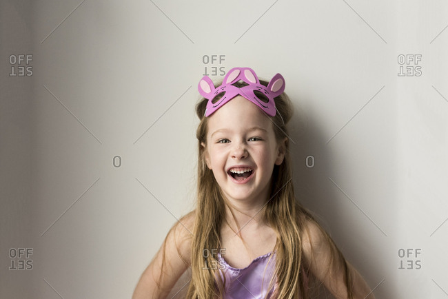 Laughing girl with bunny rabbit headband against while wall