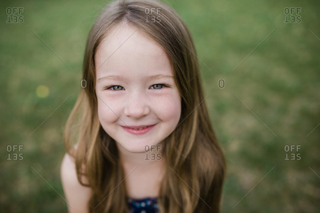 Close up of cute girl standing in grass looking at camera and smiling