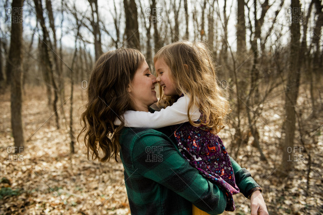 Smiling mother & young daughter embrace nose to nose in woods in Fall
