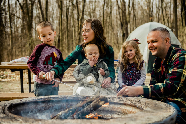Smiling family roasting marshmallows over campfire in woods during Fall