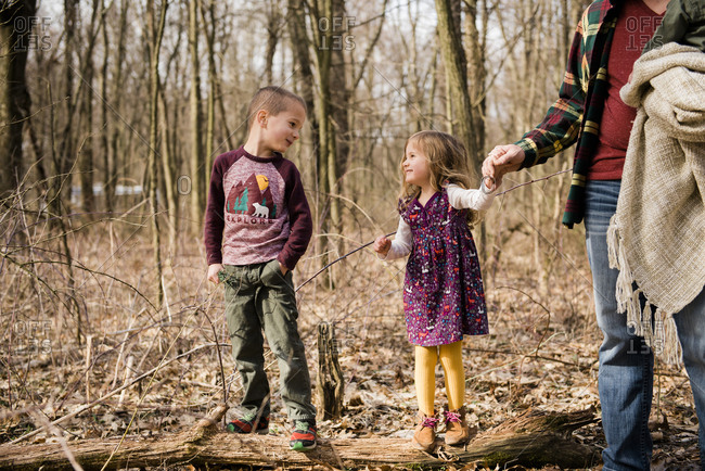 Brother and sister smile at each other in woods holding dad's hand