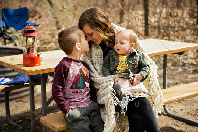 Smiling mother cuddles sons camping in fall picnic area