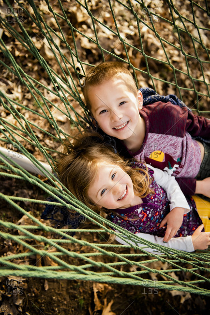 Smiling brother and sister relax in hammock in Fall looking at camera