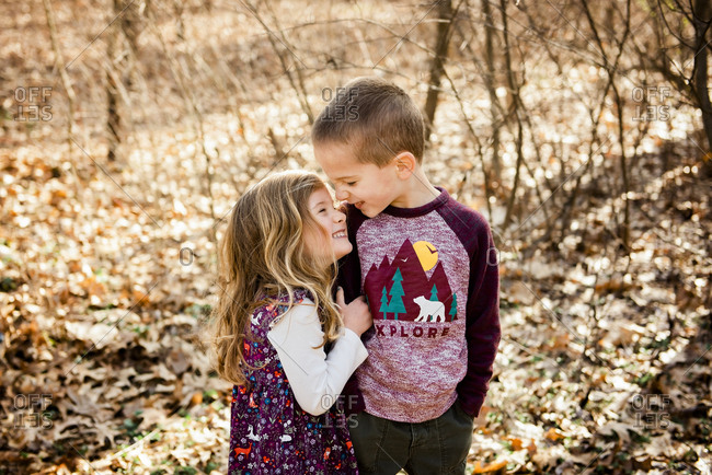 Smiling brother and sister stand in fall leaves with noses together