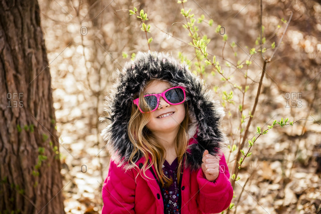 Smiling girl wears sunglasses dancing in woods during Fall