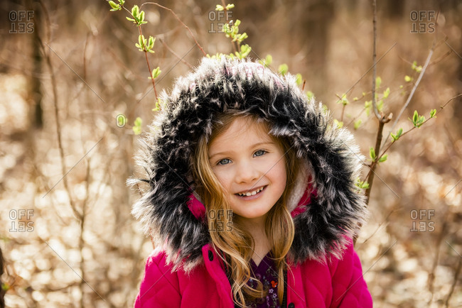 Smiling girl looks at camera with fur hood on head in Fall forest