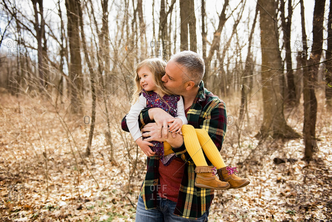 Loving father holds and kisses smiling daughter on cheek in Fall woods