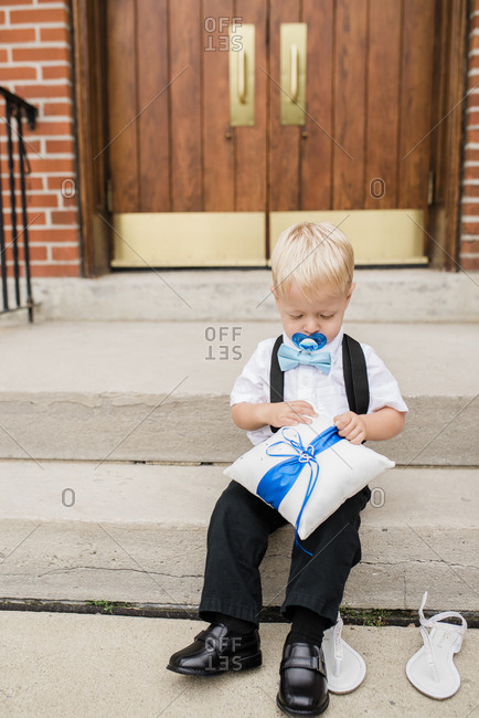 Toddler ring bearer with pacifier sits on steps of church