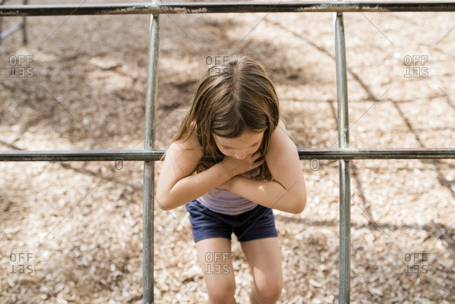Young girl with brown hair plays on playground in summer on sunny day