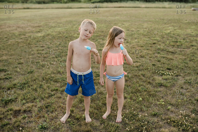 Brother and sister eat popsicles wearing swimsuits in grass in summer
