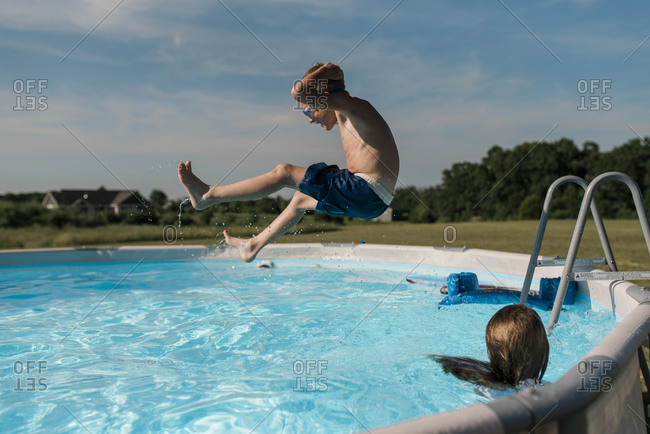 Young boy jumps into pool on a sunny summer day in the backyard