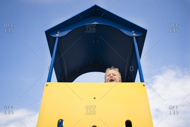 Young laughing boy looks down from playhouse in blue sky