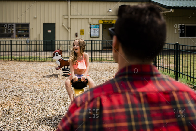 Young Girl laughs playing on seesaw with uncle on sunny day