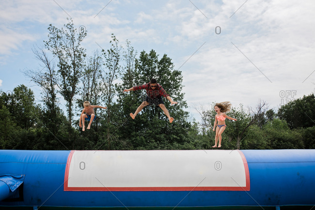 Young adult man and two children jumping on sunny day against blue sky