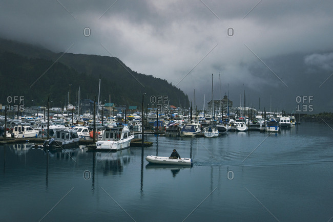 Whittier, Alaska, United States - September 16, 2018: Long man in boat sails into Whittier harbor on a rainy day