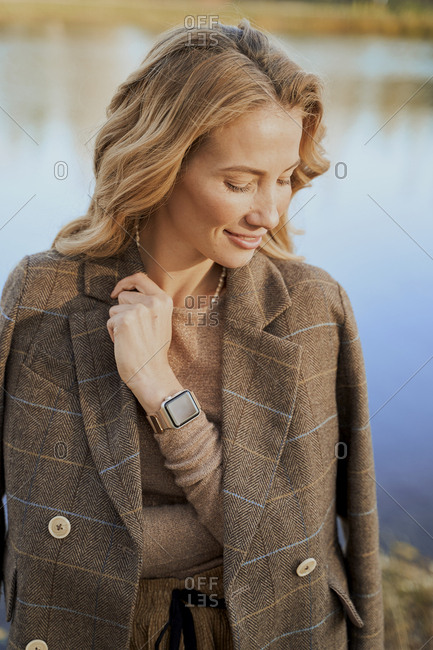 Happy cute business woman blonde outdoors, smart watch on hand.