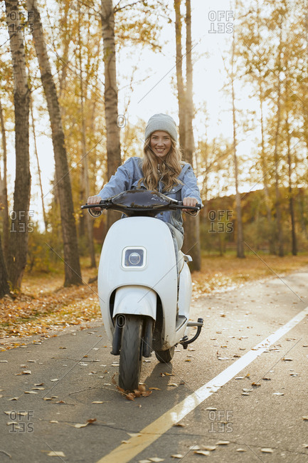 Strong confident woman rides an electric scooter while holding her hands on the steering wheel.