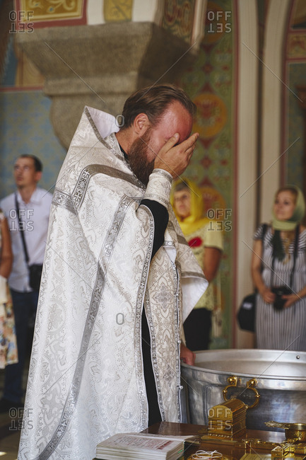 Krasnoyars, Russia - August 4, 2019: The holy father stands washing his face with holy water at a Russian Orthodox Christian church