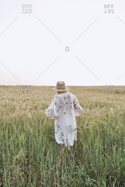 Strong confident woman traveler in dress and hat walks on a wheat field view of the back