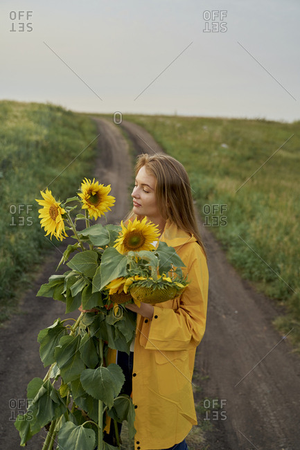 Beautiful woman traveler blogger in a yellow raincoat and yellow sunflowers on the road in a field