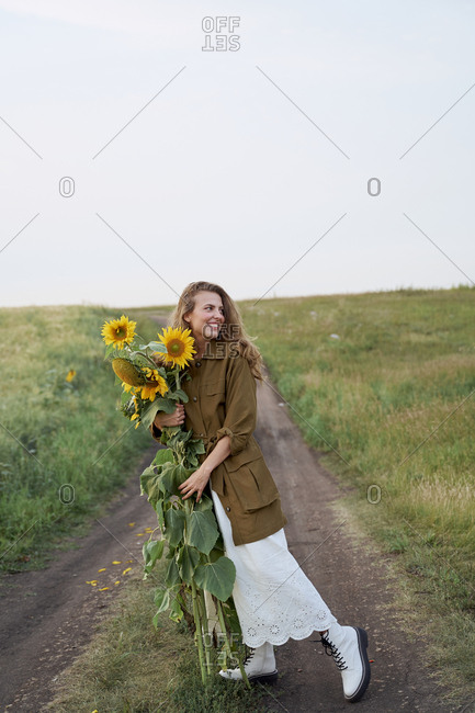 Beautiful woman traveler blogger in a jacket and yellow sunflowers on the road in a wheat field