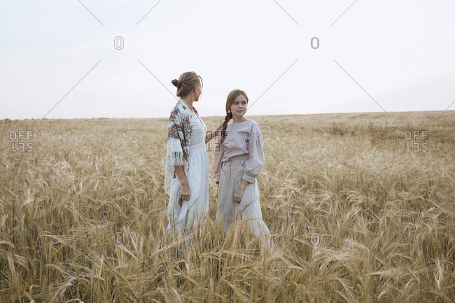 Beautiful sisters women travelers in dresses and Russian national shawls in a wheat field like peasants