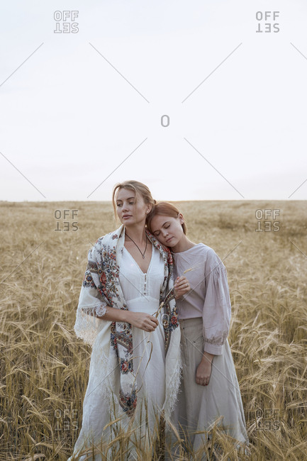 Two beautiful sisters women stand in dresses and Russian national shawls in a field of wheat as farmers