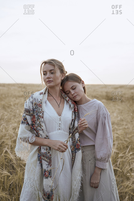 Two beautiful sisters women stand in dresses and Russian folk scarf in a field of wheat as farmers