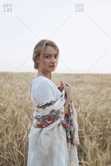 Beautiful young woman stands in a dress and Russian national scarfs in a wheat field looks at the camera