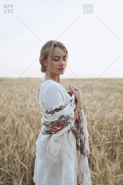 Beautiful young woman stands in a dress and Russian national scarfs in a wheat field looks down