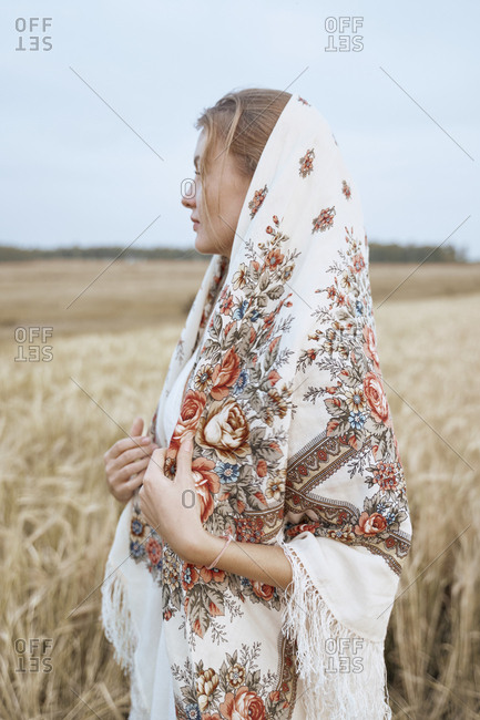 Beautiful woman from the village stands in a dress and Russian folk scarf in a wheat field