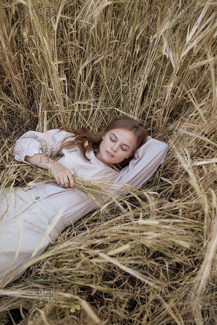 Beautiful teenager girl lies in a dress and Russian folk dresses in a wheat field