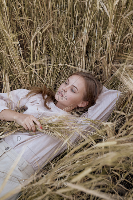 Beautiful teenager girl lies in a dress and Russian folk scarf in a wheat field
