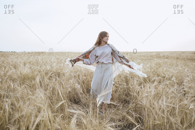 Beautiful young woman dancing in a dress and Russian national shawls in a wheat field
