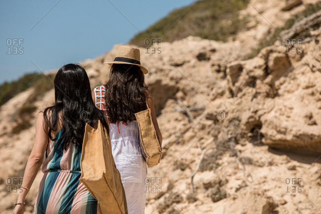 Rear view of two women with long dark hair walking on beach