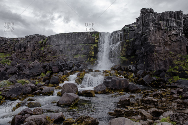 Waterfall flowing over rocky cliff in Iceland