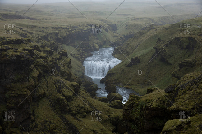 Aerial view over waterfall flowing in rural Iceland