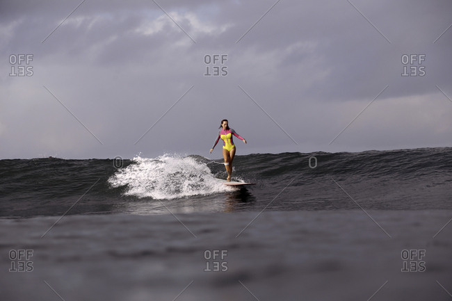 Female surfer on a wave, Bali, Indonesia