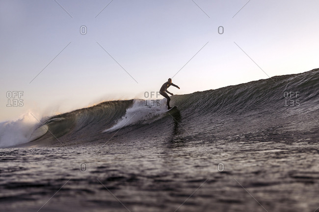 Surfer on a wave at sunset time, Bali, Indonesia
