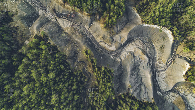 Bird's eye view of a dry lake surrounded by green trees in Monte Perdido, Spain