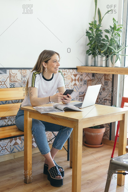 Smiling young woman sitting at wooden table at a cafe working on laptop