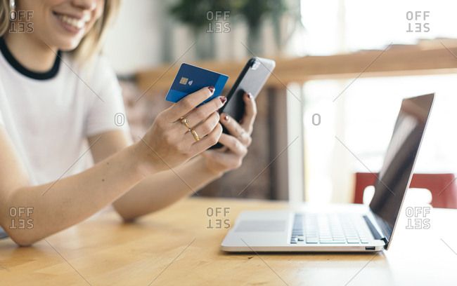 Young woman using credit card and her Smartphone to make a payment