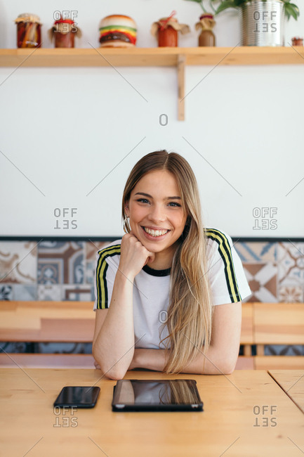 Portrait of a smiling young woman in a cafe sitting at table with tablet and Smartphone