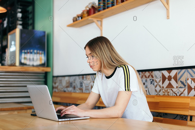 Young woman at a cafe working on her laptop